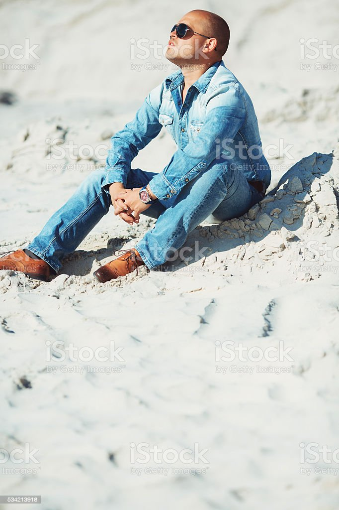 glasses lies in jeans clothes on the sand in Dubai royalty-free stock photo