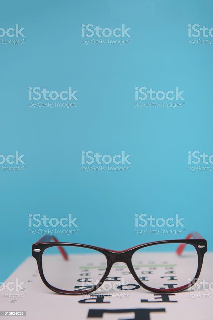 glasses lying on snellen test chart stock photo