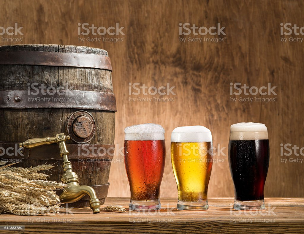 Glasses of  beer and ale barrel on the wooden table. stock photo