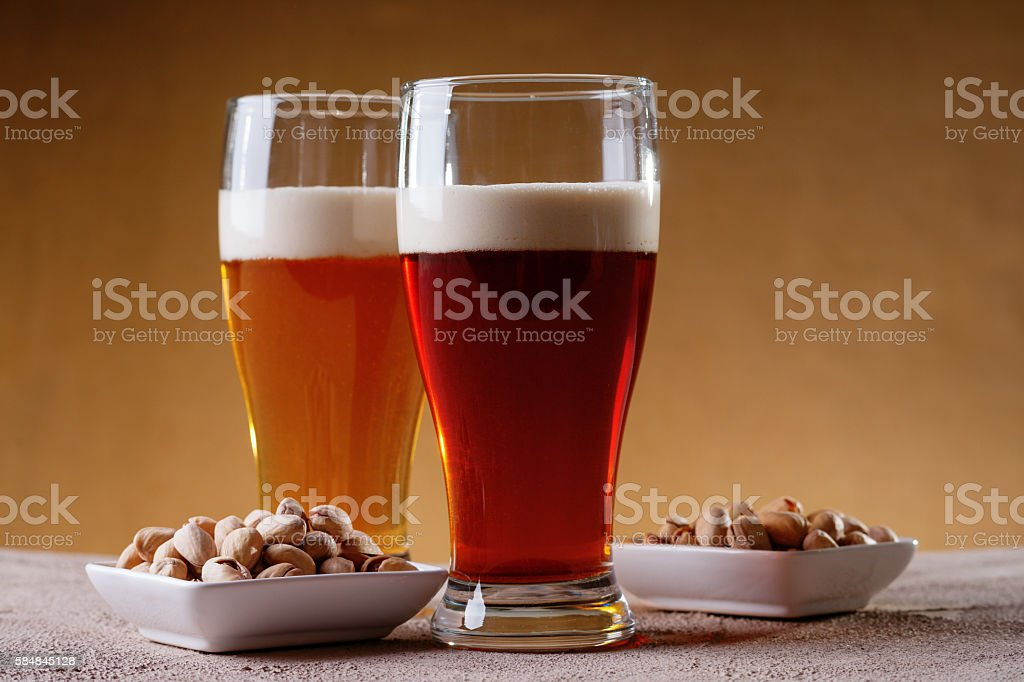 Glasses of beer and pistachio nuts stock photo