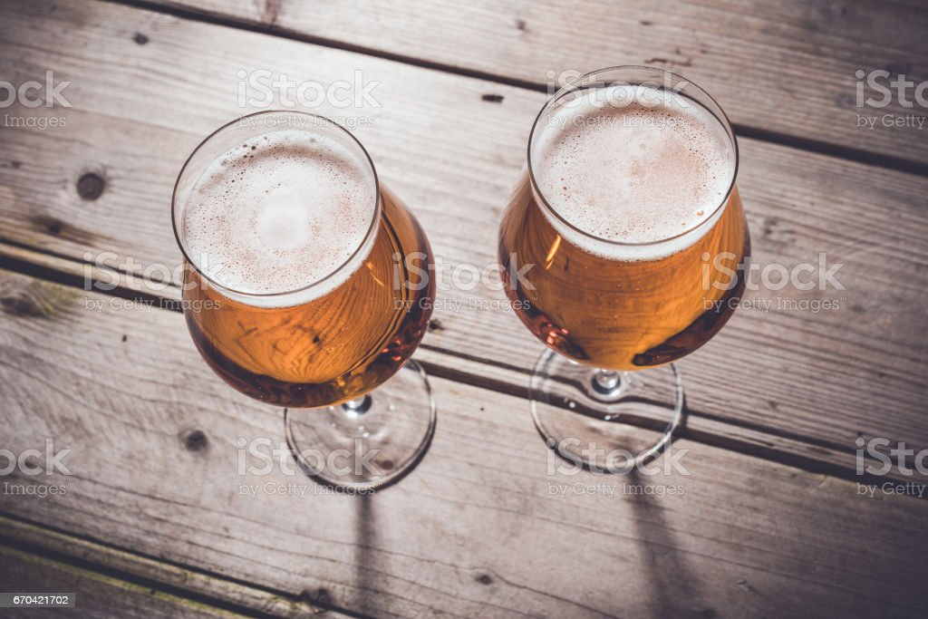 Glasses of beer on an old wooden table. stock photo