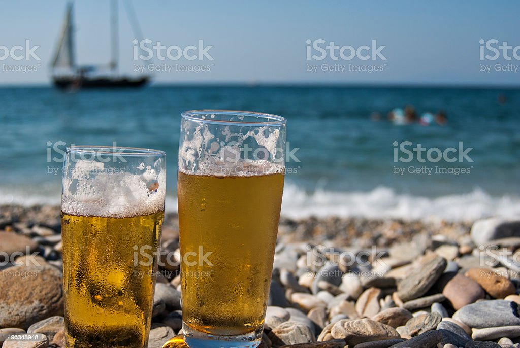 Glasses of beer on the beach stock photo