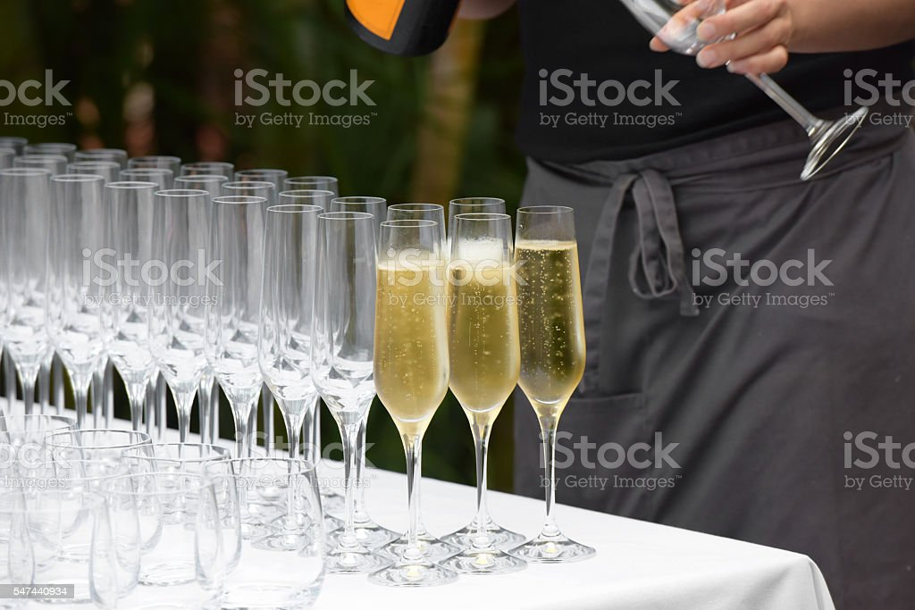 Glasses of champagne being filled with bottle visible stock photo