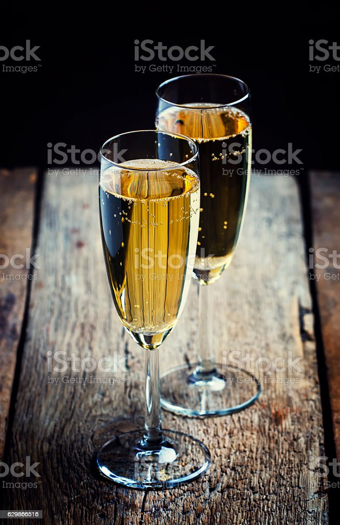 Glasses of champagne on the old wooden table stock photo