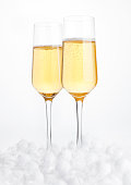 Glasses of champagne with bubbles on snow
