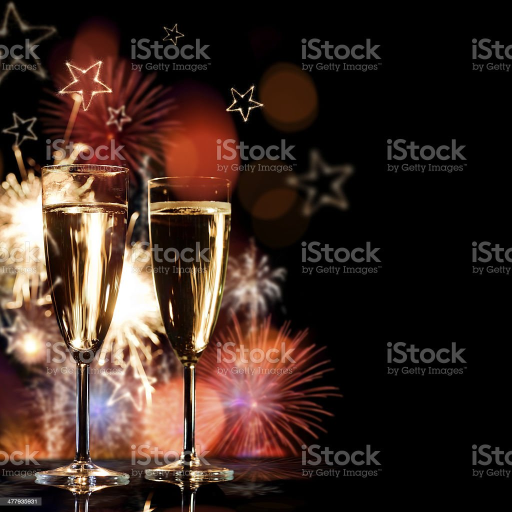 Glasses of champagne with fireworks in background royalty-free stock photo