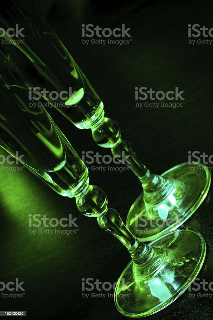 Glasses of champagne with green disco lights royalty-free stock photo