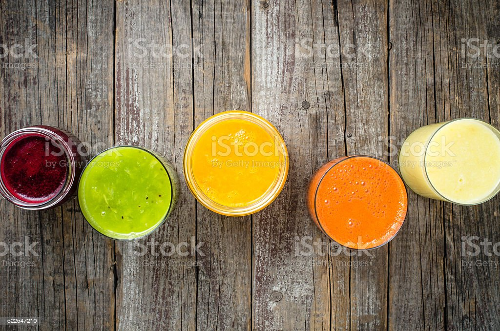 Glasses of fresh juice on wooden table stock photo