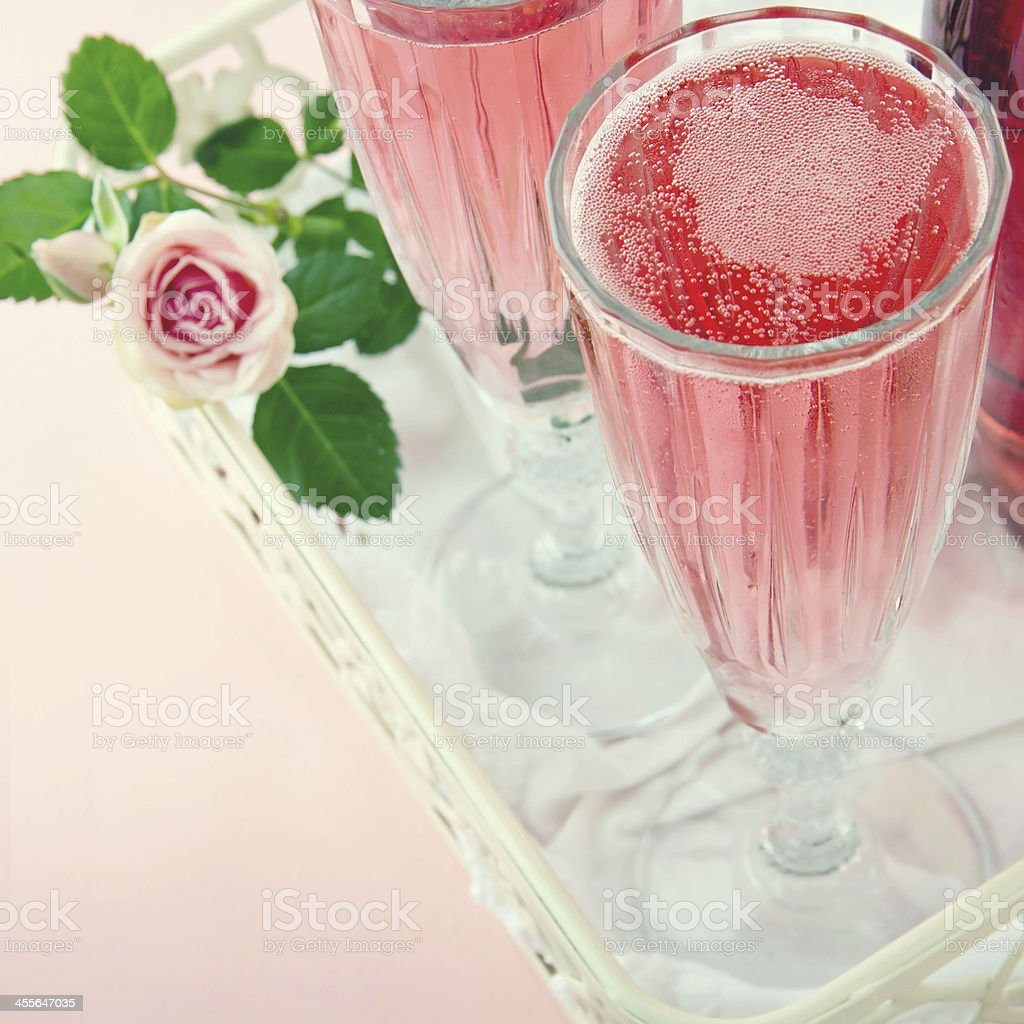 Glasses of pink champagne with a rose stock photo
