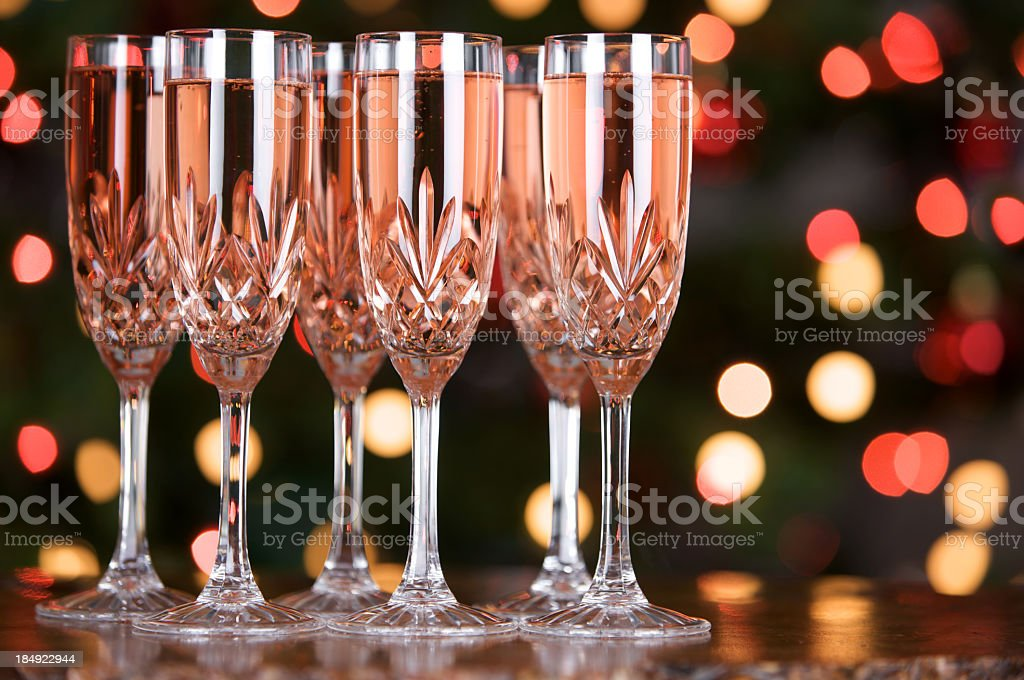 Glasses of pink champagne with coloured defocused lights in background stock photo