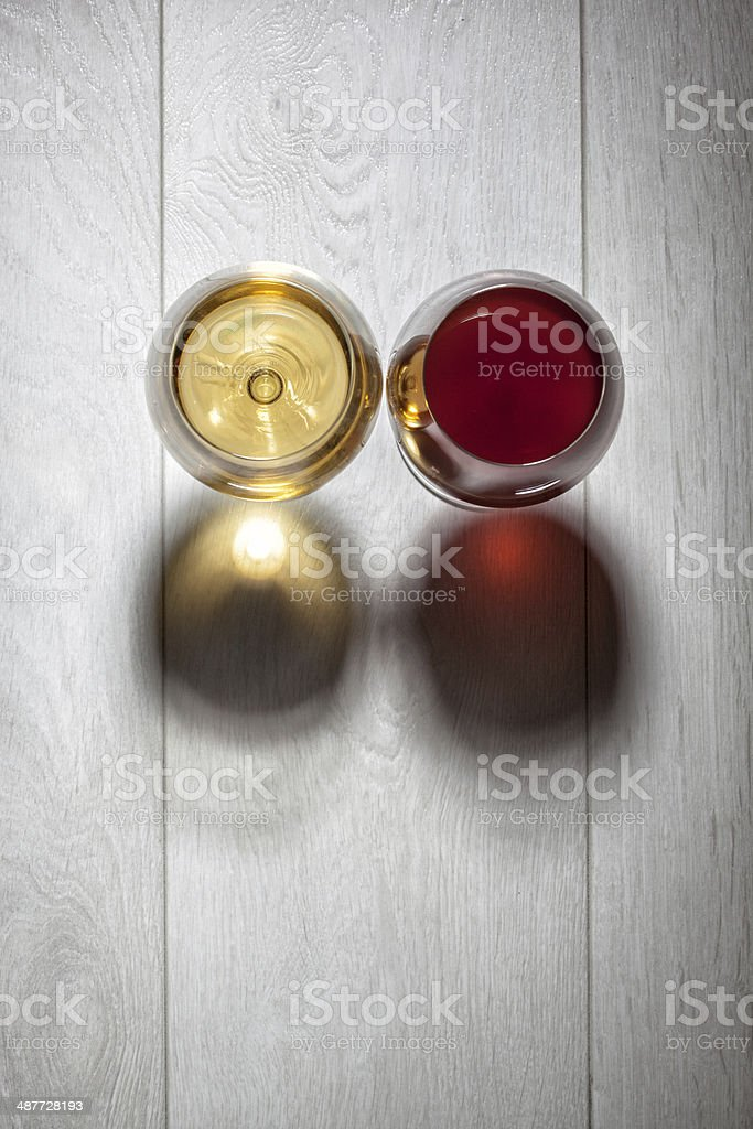 Glasses of red and white wine on wooden table stock photo