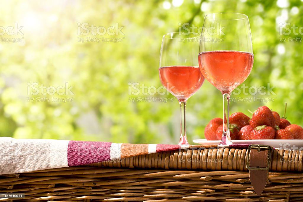 Glasses of rose wine and a plate of strawberries on a picnic stock photo