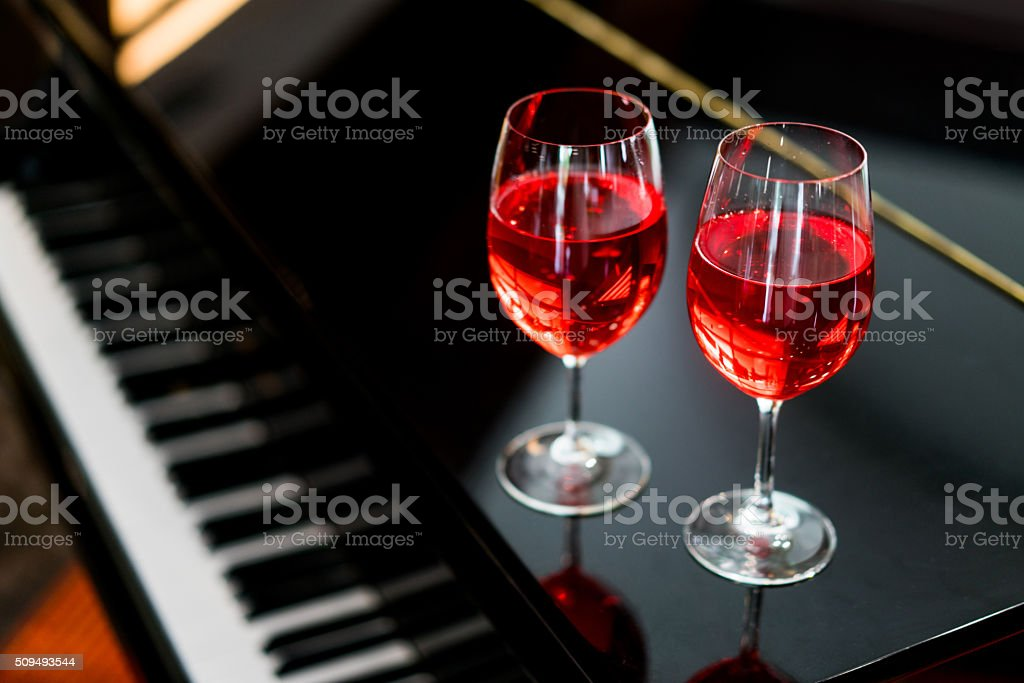 Glasses of rose wine on a piano stock photo