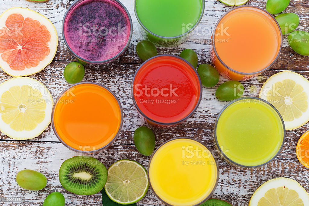 Glasses of tasty fresh juice, on wooden desk stock photo