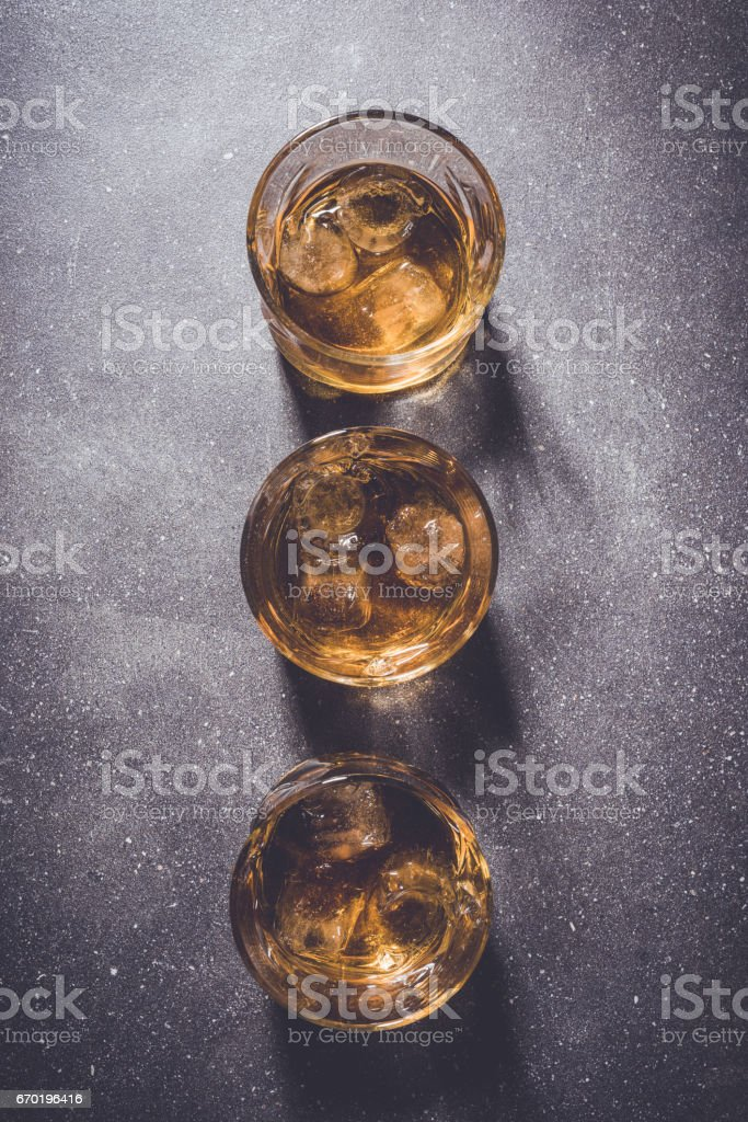 Glasses of whiskey on gray stone background. stock photo