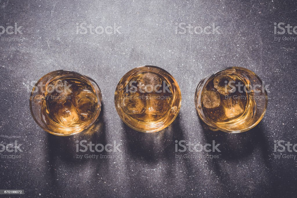 Glasses of whiskey on gray stone background. stock photo