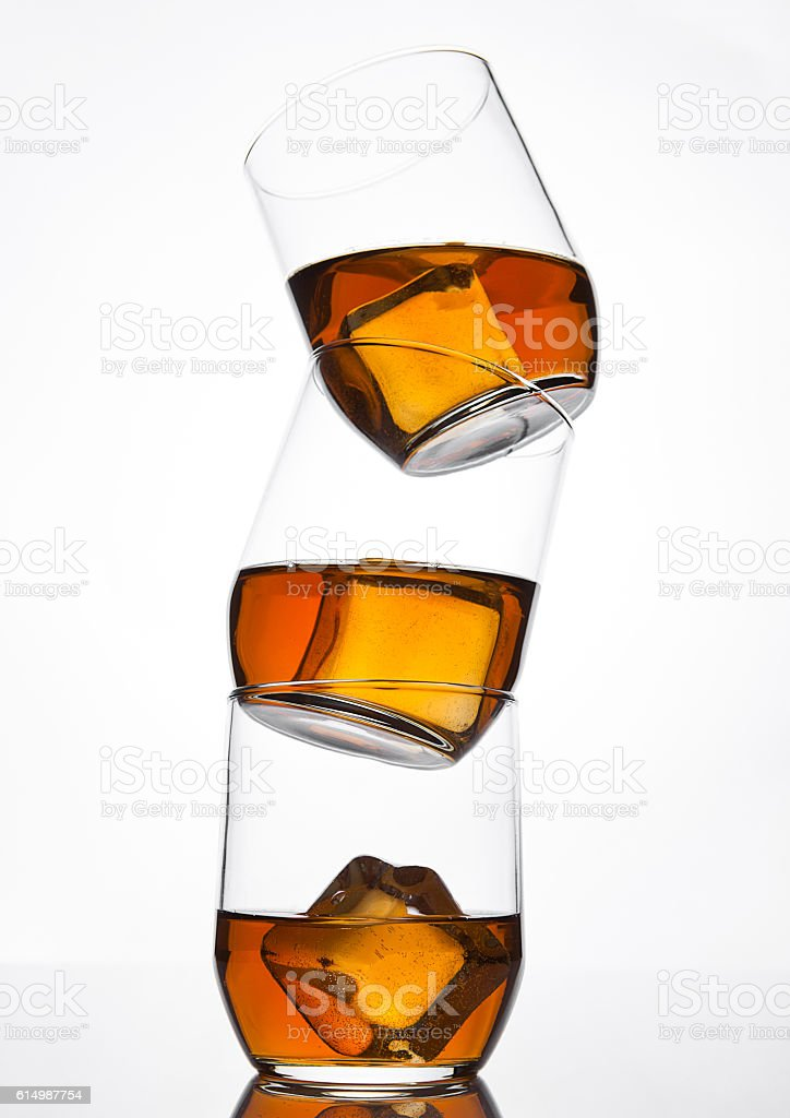 Glasses of whiskey with ice cubes and reflection stock photo