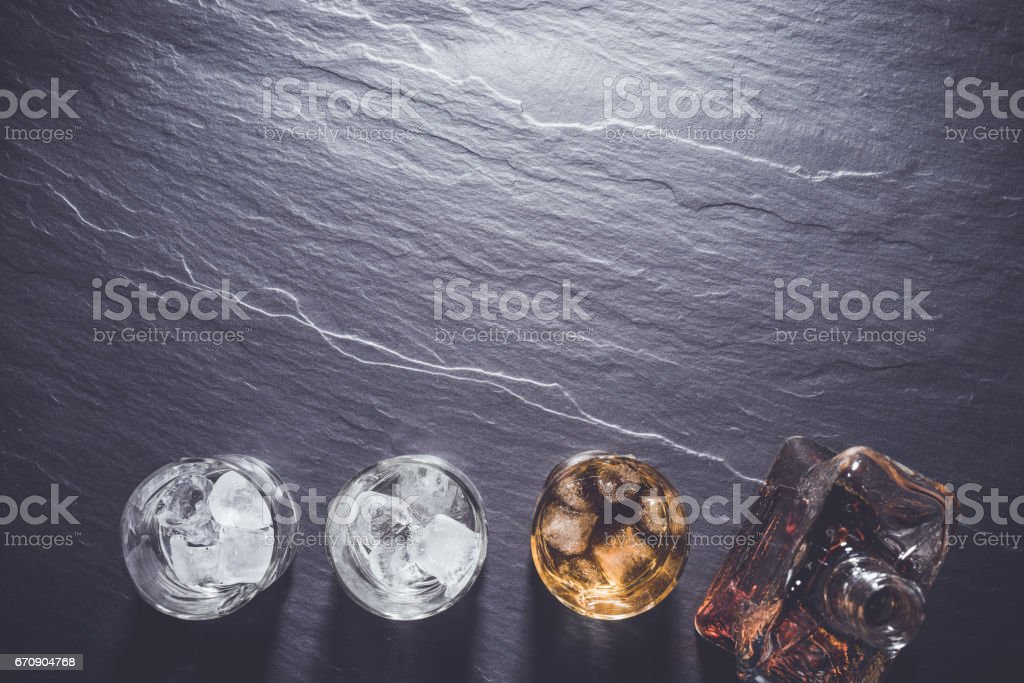 Glasses of whiskey with ice cubes on stone table. stock photo