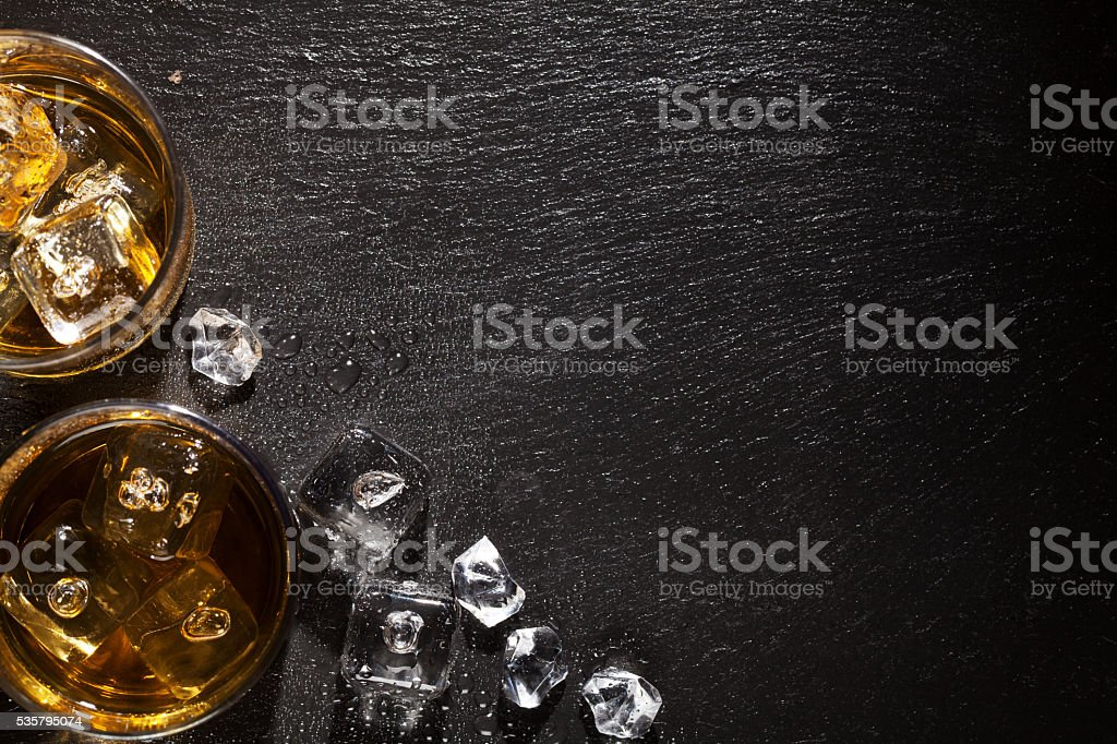 Glasses of whiskey with ice on black stone table stock photo