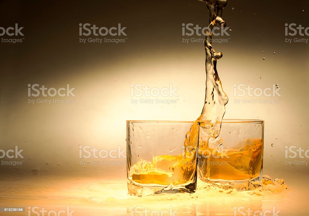 Glasses of whiskey with splash stock photo