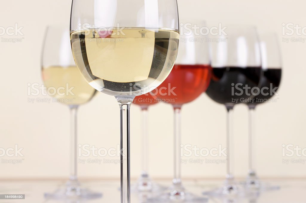 Glasses of white, red and Rose wine stood on table royalty-free stock photo
