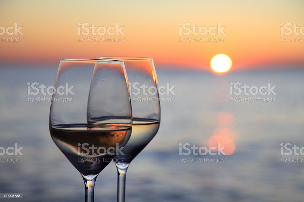 Glasses of wine against red sunset stock photo