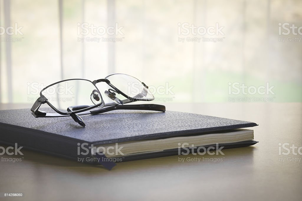 Glasses on a book stock photo