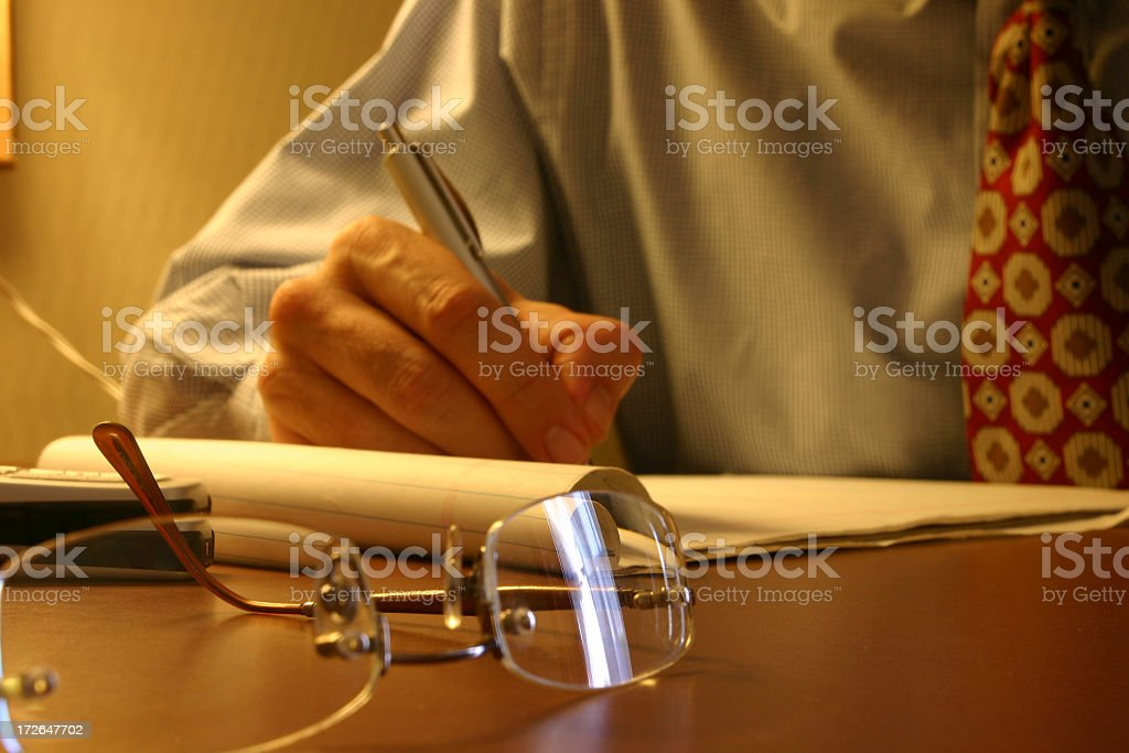 Glasses on a desk next to mans hand writing on a notepad royalty-free stock photo