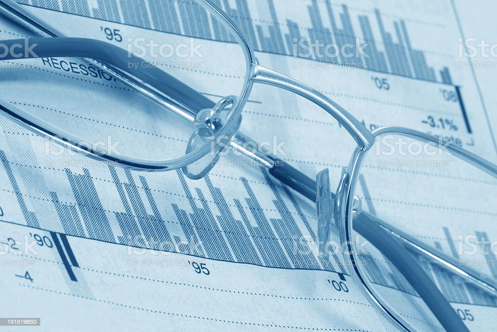 Glasses on diagrams (blue toned) royalty-free stock photo