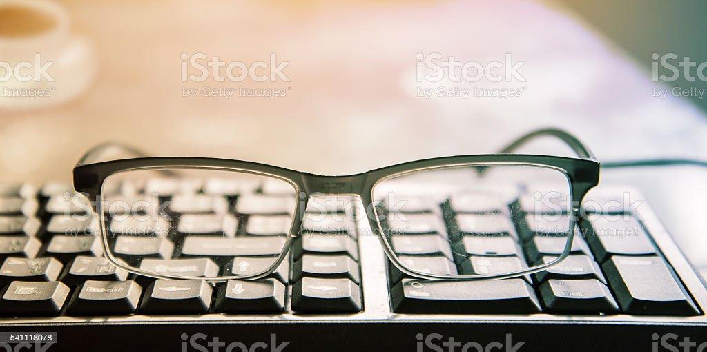 glasses on keyboard stock photo