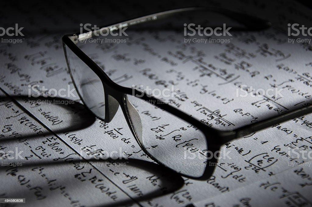 Glasses on mathematical formulas stock photo