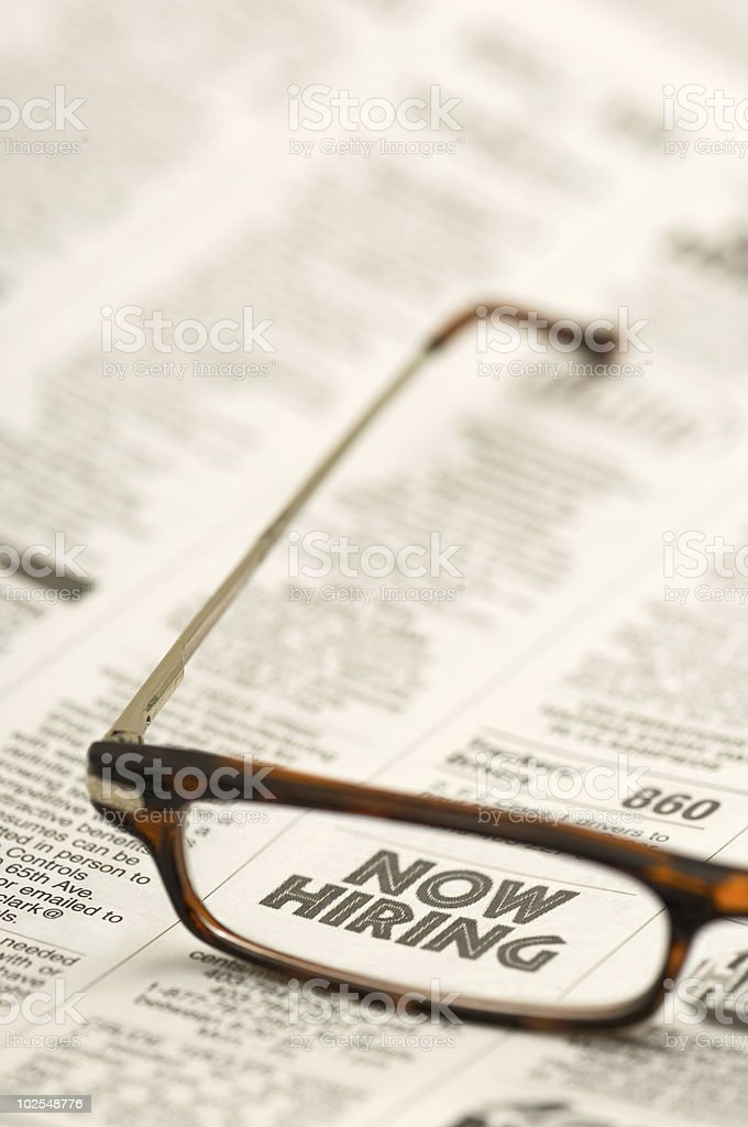 Glasses on newspaper ad: Now Hiring royalty-free stock photo
