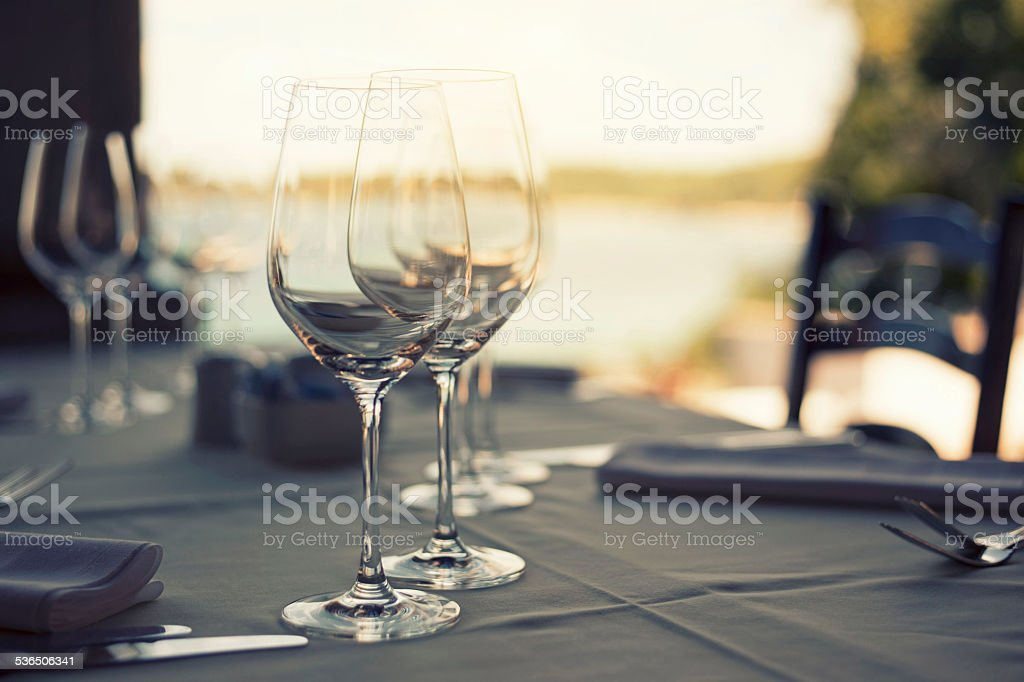 Glasses on the restaurant table near the sea stock photo
