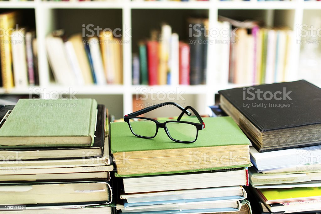 Glasses on top a pile of books stock photo