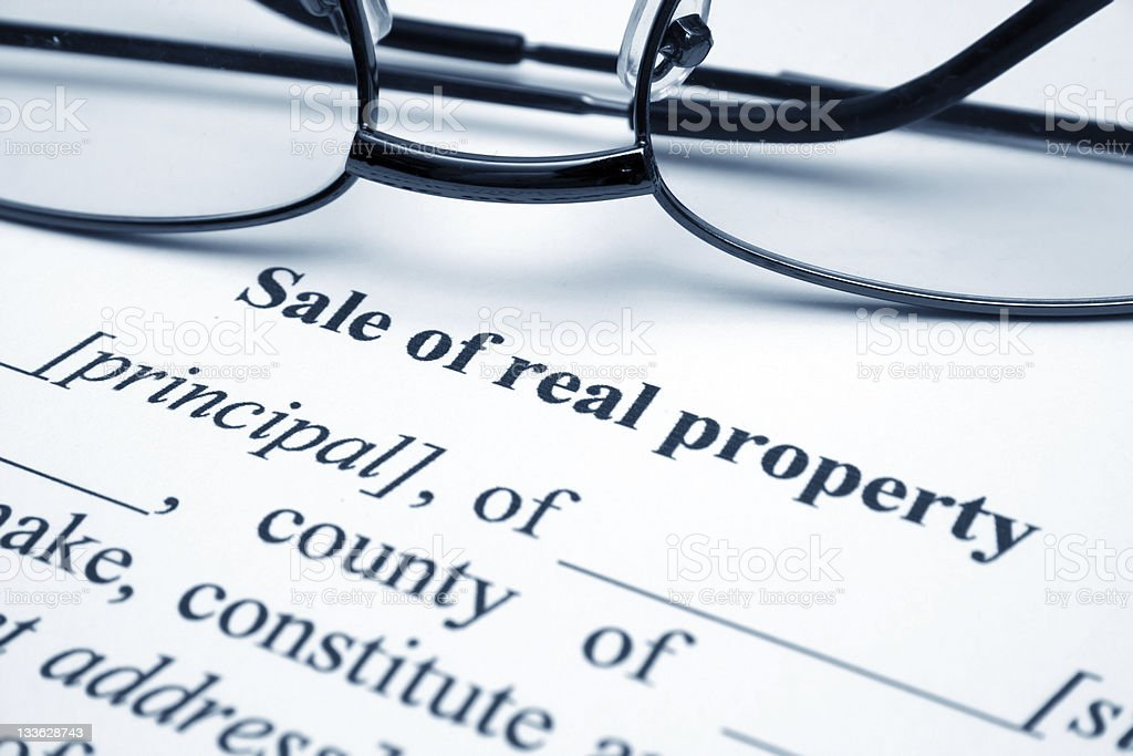 A glasses on top of a form for sale of real property royalty-free stock photo