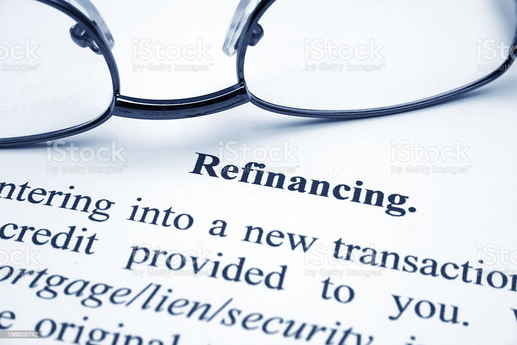 Glasses on top of the written definition of refinancing royalty-free stock photo