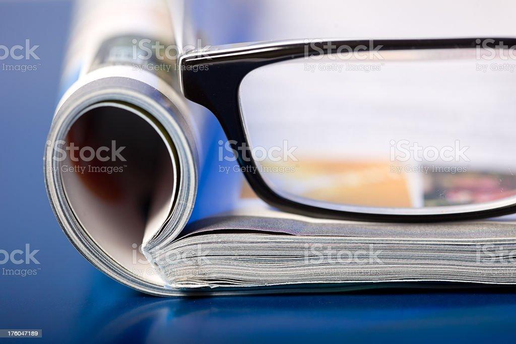 Glasses sitting on an open magazine stock photo