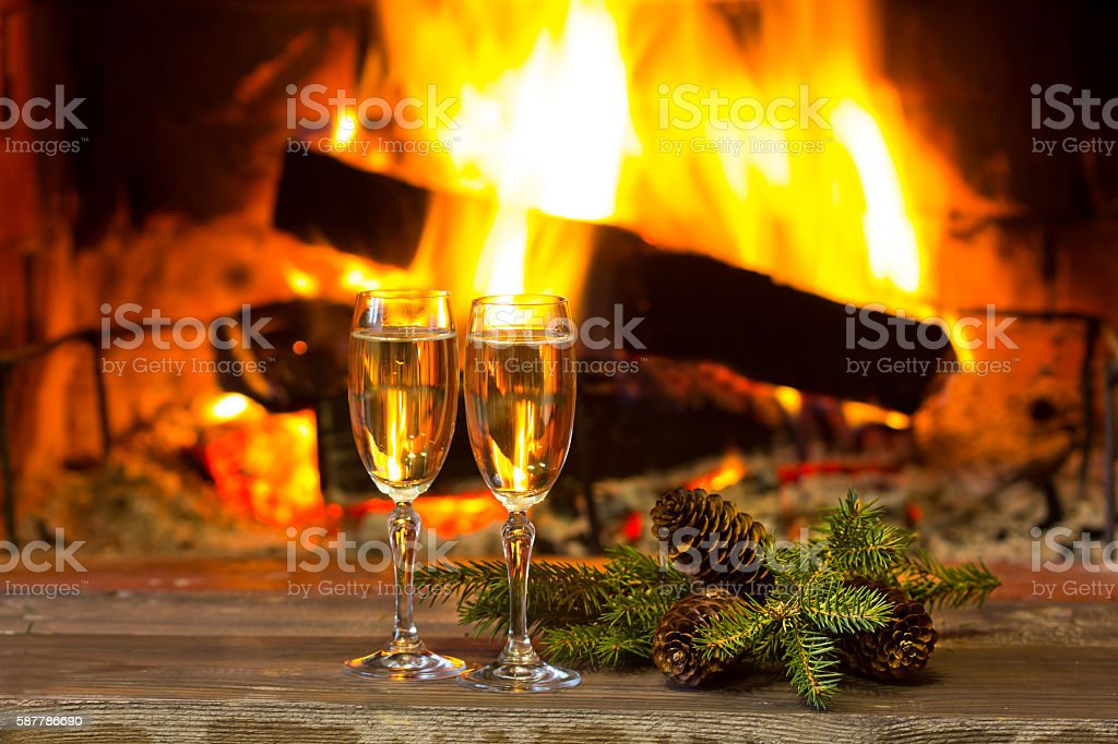 Glasses sparkling wine, fir branches, fireplace. New Year Christmas concept stock photo