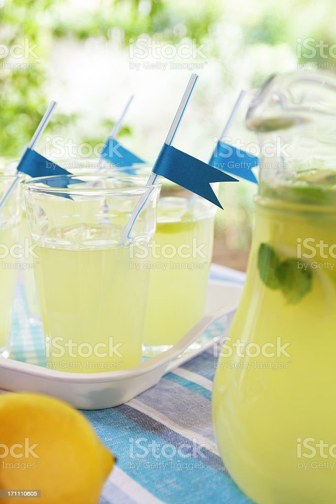 Glasses with fresh lemonade on a table at the garden. stock photo