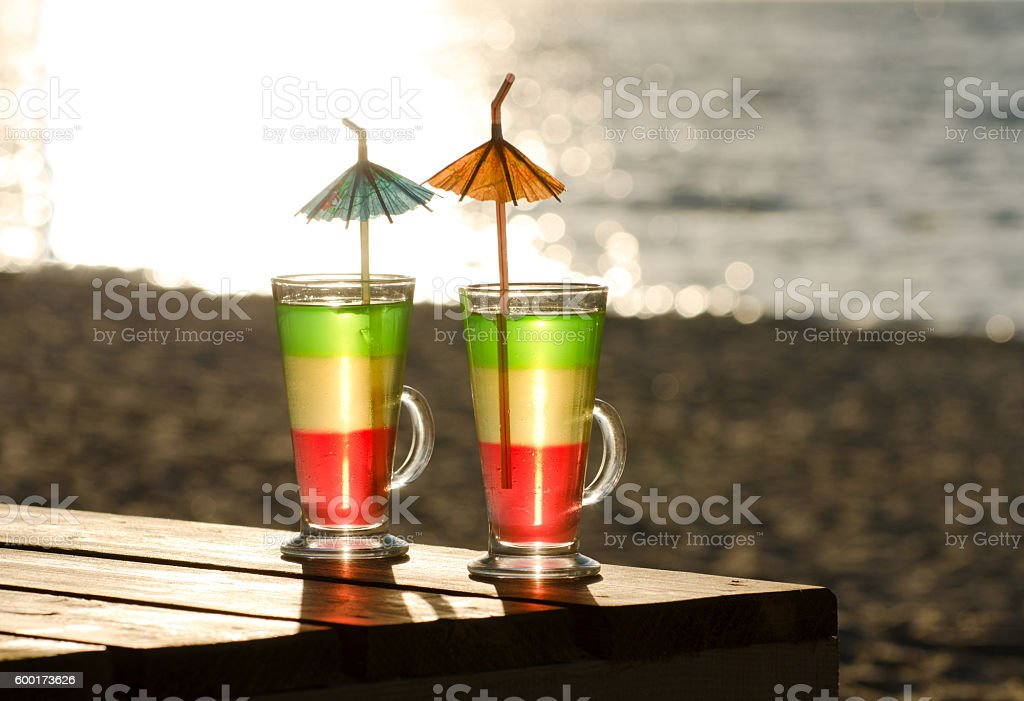 Glasses with multi-colored cocktails on the beach stock photo