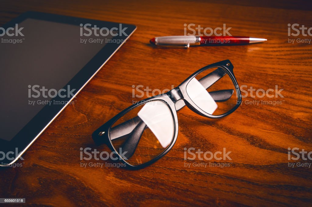 Glasses with pen and tablet on a wooden natural table. Home office....
