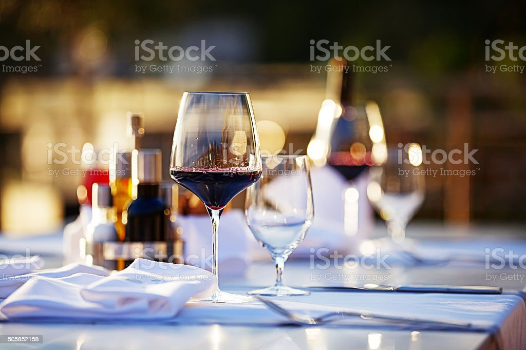 Glasses with red wine at sunset stock photo