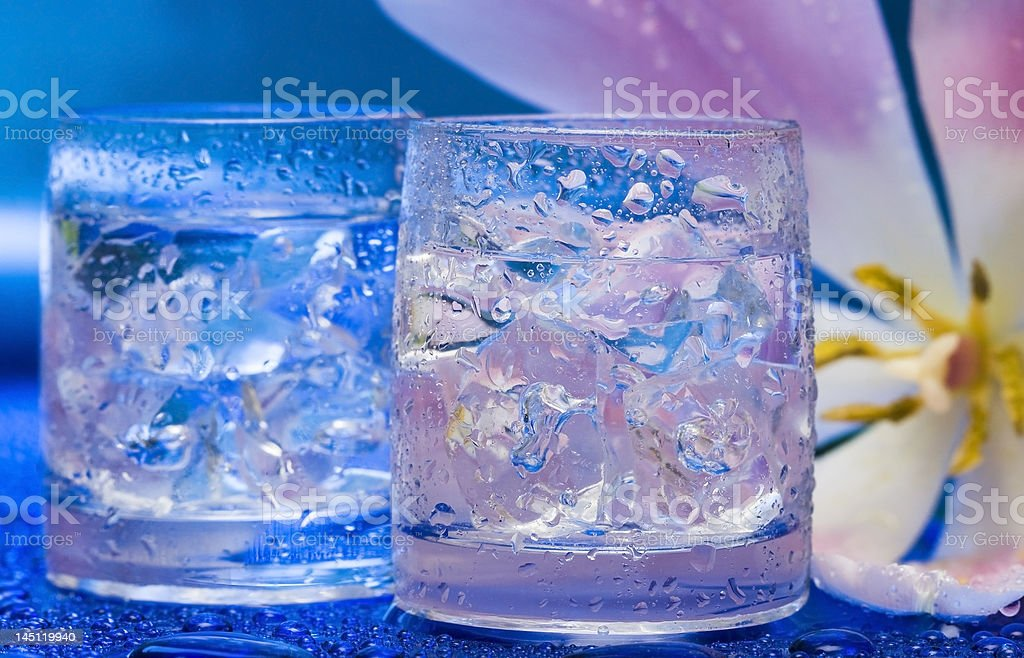 Glasses with water and flower over blue royalty-free stock photo