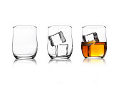 Glasses with whiskey and ice cubes and empty glass