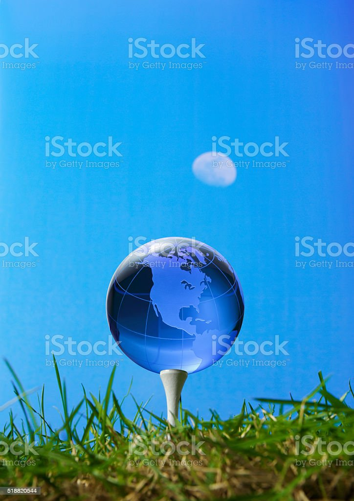 Glassy globe on tee in grass and Midday moon stock photo