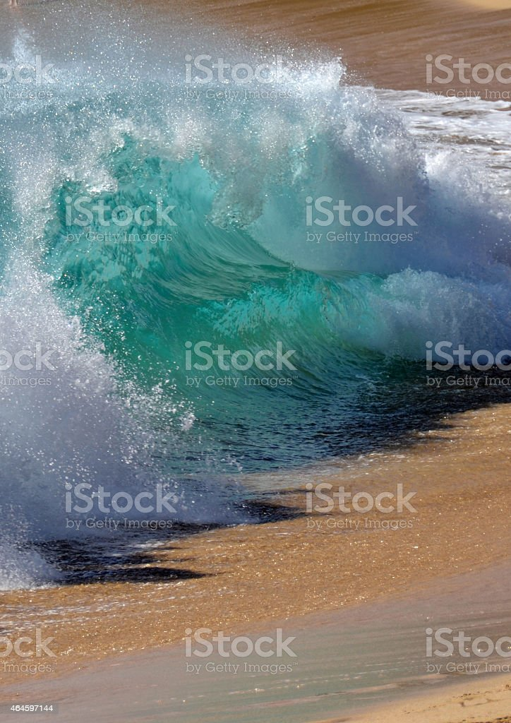 Glassy wave breaks on the beach stock photo