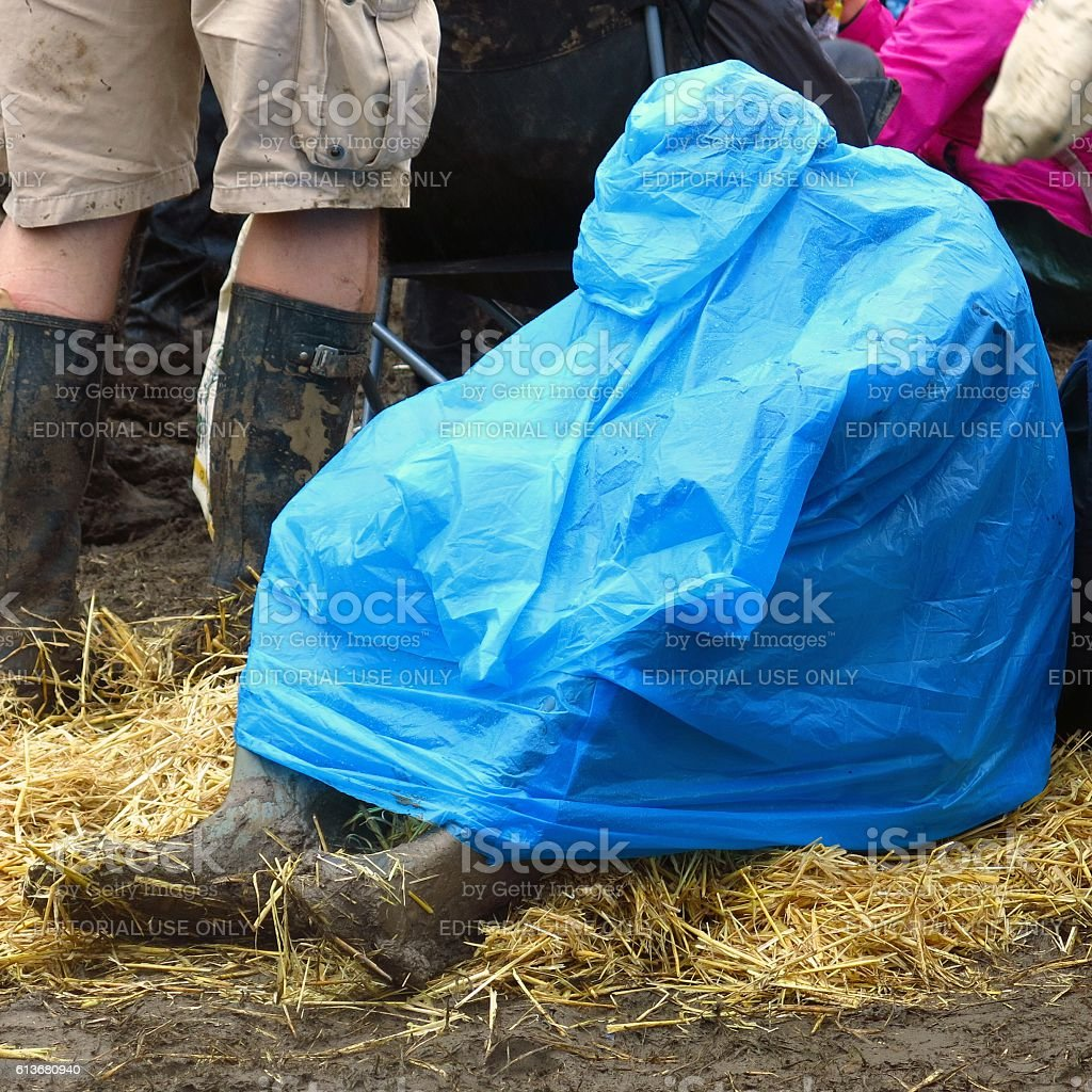 Glastonbury Festival man in blue poncho prepared for rain stock photo