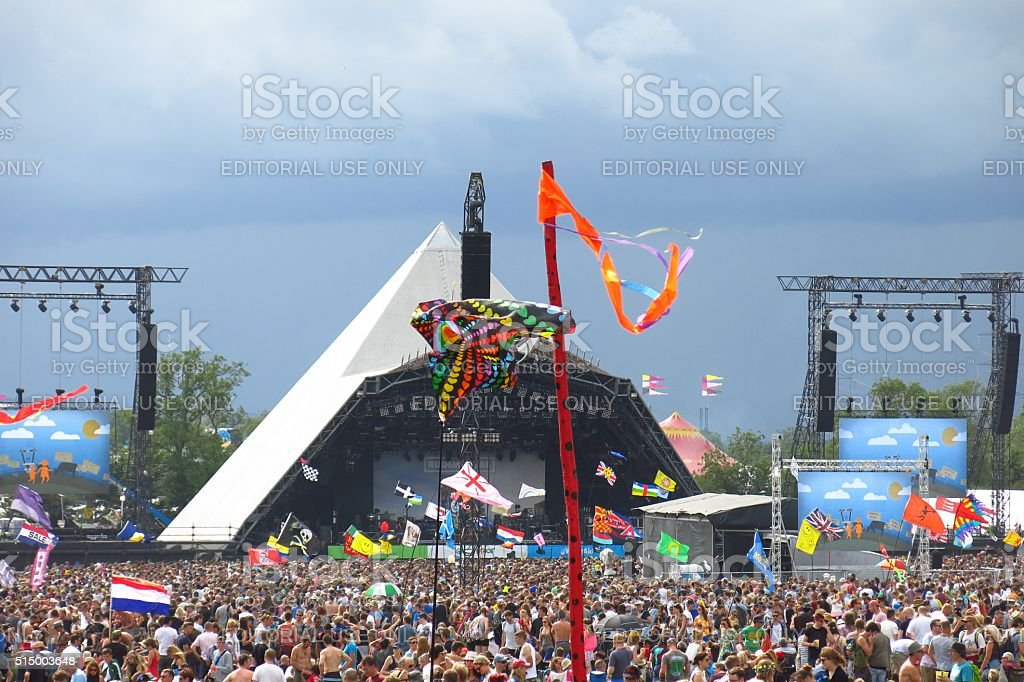 Glastonbury Festival music festival Pyramid Stage crowds stormy sky stock photo