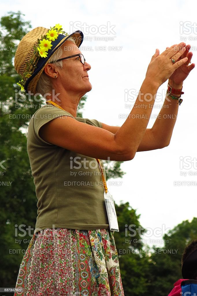 Glastonbury Festival older woman in daisy hat stock photo
