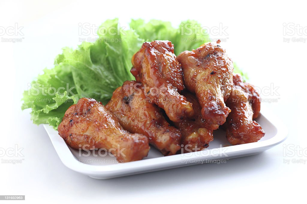 BBQ glazed wings served on a white plate with lettuce stock photo